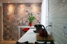 """Ainda na cozinha, uma parede composta de azulejos, que imitam ladrilhos hidráulicos (da Portinari), destaca-se. O piso, muito parecido com a da sala, não é laminado, mas sim um porcelanato (Portobello) que imita madeira. """"Ele foi escolhido nessa tonalidade para transmitir a ideia de continuidade"""", explica Gláucio."""