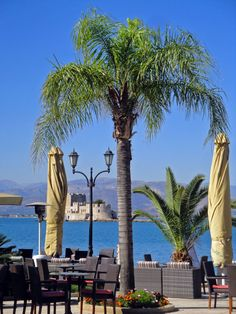 Outdoor tables of seaside Napoli di Romania cafe in #Nafplio with #Bourtzi fortress in the background. #Peloponnese - #Greece