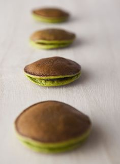 Dorayaki (どら焼き, どらやき, 銅鑼焼き, ドラ焼き)  a japanese confection consisting of two small pancake-like patties made from castella wrapped around a filling of sweet bean paste and matcha tea.