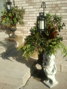 Clever Christmas outdoor urns with lanterns hung from shepherd hooks above the greenery (uploaded to Pinterest).