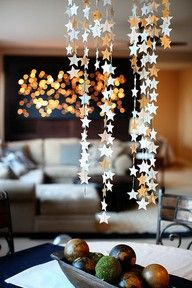 DIY Star mobile...  Create a rain of stars over the festive table, cutting paper asterisks & join together with clear fishing line then hang them on a circular base of wire or a twig!... Or decorate with the lights around a large branch >>sandrakleist.blogspot.com