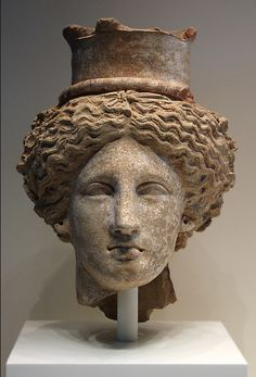 Head of Demeter or Kore  Greek, made in Sicily, 350-300 BC  Terracotta    Inventory # 76.AD.34    The worship of Demeter (goddess of agriculture) and her daughter, Kore, was popular in Sicily. The island was famous in antiquity for its fertile fields, which supplied grain to the rest of the Greek world. This head, broken from a bust or a full-length statue, would have been left as an offering in one of Demeter's many sanctuaries and temples.