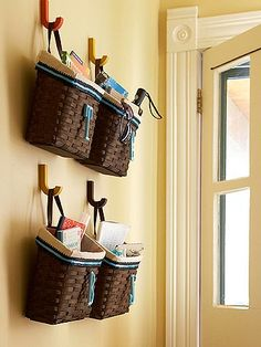 Simply attach a handle on some baskets and place them on hooks for easy door organizers. Place the baskets near an entrance way for on-the-go necessities like mail, magazines, umbrellas, glasses, and more. #diy #organize