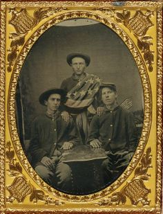 Three unidentified soldier buddies in front of painted backdrop showing 34-star American flag. Patriotic union facer plate framing photo. (Library of Congress, Liljenquist Family Collection of Civil War Photographs).
