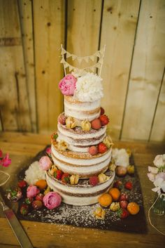 Four tier naked sponge cake decorated with fresh fruit and flowers | Photography by http://www.modernvintageweddings.com/