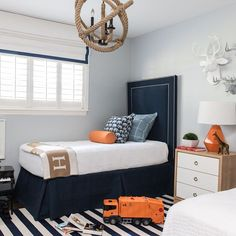 Blue and orange kid's room boasts pale blue walls lined with tall navy blue velvet headboards with ...