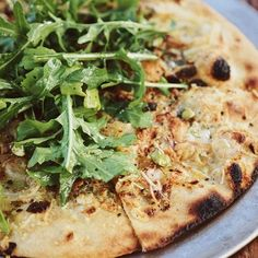 PIZZA OF THE WEEK: Roasted garlic, leeks, white onions and shallots with Gorgonzola, pistachios, arugula and a olive oil drizzle.