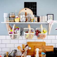A wall shelf and three baskets filled with containers of dry food and fruit.