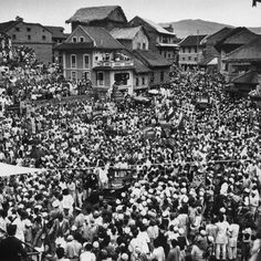 Edmund Hillary and Tenzing Norgay, the first men to summit Mt. Everest, ride into a welcoming throng in Temple Square of Bhandgaon, 1953.