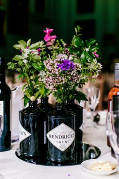 Centrepiece Gin Bottles Floral Flowers Purple Mirror Centre Hendricks Stylish Sassy Gin Wedding http://epiclovestory.co.uk/