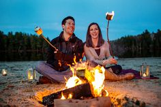 Fall engagement photos of a great outdoors loving couple roasting marshmallow by a campfire at the beach / lake in Upstate, NY
