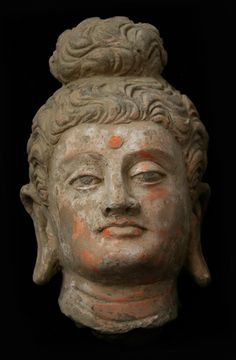 A beautiful terracotta head of Buddha modeled in the classical Hellenistic style. Pakistan 3rd - 4th c. Kushan Period Gandharan Region
