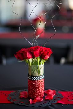 DIY centerpieces for red and black wedding Dollar Tree vase painted with Modge Podge, covered in red glitter, then sprayed with a glitter sealant clear spray paint by Krylon. Ribbon hot glued on. Fresh roses ordered from Sam's Club. Black glitter curly tings from Amazon (also sealed with clear spray paint to avoid glitter getting everywhere)