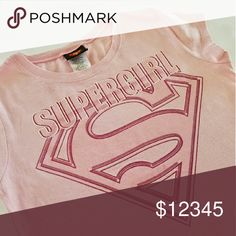 """Supergirl"" Hero Pink Tee Tshirt ""Supergirl"" pink tee in excellent condition. Very small spot as seen in photo above.  Girls' size XL (14/16).  Measures approximately 22"" L and 17"" flat across from underarm to underarm. Jerry Leigh Entertainment Apparel Shirts & Tops Tees - Short Sleeve"