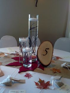 Burlap runner, felt leaf shaped placemat, wood burned wood slice table #, modge podge preserved leaves, red dog wood branches submerged in water with a floating candle on top, Indian Blanket seeds in mesh bags,