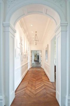 Great white hallway with great architecture and herringbone wood floors