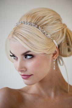 Bouffant, fancy formal hair. Simple sparkly headband. Dark eyed makeup, fair skin.