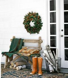 Cozy throw blankets and a wire basket filled with firewood are easy decorations to add to your front porch for the fall.