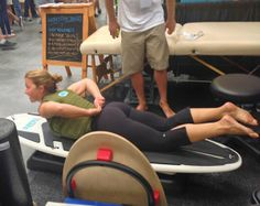 The surf physical therapists from the Waters Edge Therapy booth trying out a PaddleAir Ergo Bali Green vest at The Boardroom International Surf Show on May 17-18 at the Del Mar Fairgrounds, California.