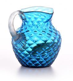 """Selkirk Auctioneers  RUBINA VERDE PITCHER.  American, late 19th- early 20th century, glass. Blue fishnet body and a clear applied handle. 5""""h.  Estimate $ 50-100"""