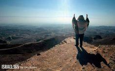 "Ilan Rosen took this impressive photo of a man raising his hands in prayer as he overlooks the Ramon Crater (the ""Maktesh"") in Israel's Negev desert."