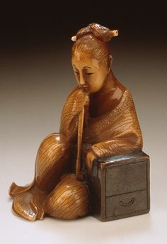 Bunga (Japan) Beauty Contemplating Love Letter, early 20th century  Netsuke, Ivory with dark staining, sumi, 1 9/16 x 1 3/16 x 1 1/8 in. (3.9 x 3.0 x 2.8 cm) Raymond and Frances Bushell Collection (AC1998.249.289)  Japanese Art Department