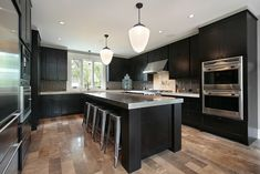 A luxury, modern kitchen with dark cabinets and stainless steel counters, appliances, and stools at the eat in island.
