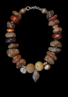 "Marion Hamilton, necklace: ""This necklace is composed of various kinds of amber: Baltic Amber (the amber in matrix), ""River Amber"" (actually copal from Africa), ""African Amber"" (bakelite from early 20th c. Germany) and Fossil Amber from Europe. The two central beads are Chinese jade surrounded by ancient and antique African amulets."" SOLD"