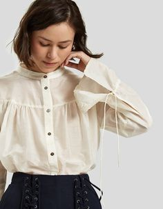 Romantic top from Farrow in Cream. Sheer fabric. Narrow band collar. Full-button placket. Long sleeves with drawstring adjustment at cuffs. Gathering at yokes and shoulders. Shirttail hem. • Voile • 72% cotton, 28% silk • Hand wash cold, dry flat