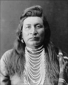 1899 Edward S. Curtis photo of a Nez Perce man. The photo is a head-and-shoulders portrait, facing front, wearing bead necklace, with blanket over shoulder.