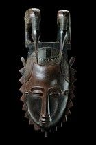 """Yaure - crowned by a pair of bird sculptures, in identical posture arranged side by side, the heads lowered and the long beaks reaching down to the forehead, slightly dam., paint rubbed off in some areas, missing part at the chin and crack on the upper rim backside, tiny missing part at the coiffure, collection number in white paint backside """"HC 633"""", on base; present mask type with the depiction of a hornbill is called """"lomane"""", which is a derivation of the word """"anoman"""", which means…"""