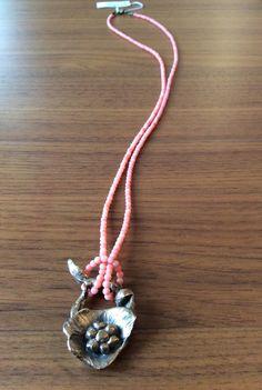 Transparent Sculptural Jewelry/Barcelona-Designed and handmade by Marta Roura. Antic Trésor Collection: Collar largo de pequeñas cuentas de coral salmón con colgante realizado en bronce en forma de flor y tallo.