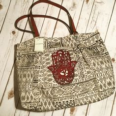 Hamsa Hand Print Canvas Large Tote This is Such a Great Bag with all the room you'll need to either travel with, overnight with or to use for anything that you would need to carry a lot of things!!! Very spacious with a zipper pocket and 2 open pockets inside. Ivory and Black with a merlot color hand. Lucky Brand Bags Totes