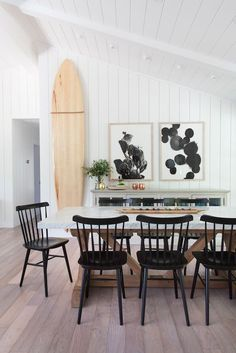 Vertical shiplap + white shiplap + white dining room + surfboard on wall + unpainted surfboard + angled ceiling + black dining chairs + wooden dining chairs + farmhouse table + x-frame table Dining Room Design, Interior Design Kitchen, Dining Area, Small Dining, Interior Decorating, Decorating Ideas, Room Interior, Kitchen Dining, Decor Ideas