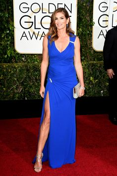 Supermodel Cindy Crawford looked like a goddess in a blue Versace gown with crystal accents for the 72nd Golden Globe Awards at the Beverly Hilton Hotel. #Versace #VersaceCelebrities