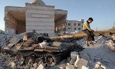 A boy plays on the gun of a destroyed Syrian army tank partially covered in the rubble of the destroyed Azaz mosques , north of the restive city of Aleppo, on August 2, 2012