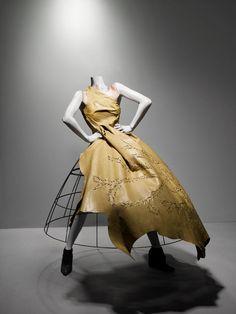 Alexander McQueen -   Ensemble:   Eshu, autumn/winter 2000–2001.   Dress of beige leather; crinoline of metal wire.