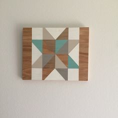 + This wall hanging features a hand-painted geometric pattern reminiscent of a barn quilt. This versatile piece with simple, clean lines fits with