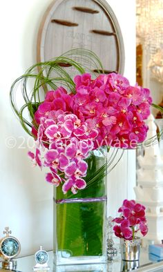 Empty Vase Florist / Vanda  Description:	Luscious Vanda and Phalaenopsis orchid stems arranged with steel grass in a slim rectangular glass vase.