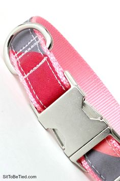Pink dog collar with red and grey stripes.