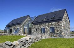 two stone cottages become one via a glass staircase