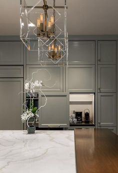 Beautifully designed contemporary gray and white kitchen is fitted with stacked gray floor-to-ceiling cabinets finished with a concealed coffee station positioned beside a wall mounted stainless steel oven fixed beneath a stainless steel microwave.