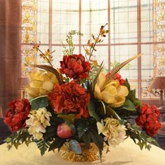 "Burgundy and gold Silk Magnolia Centerpiece AR341 - Express yourself! Red and gold hydrangea burst with color among pears, orchids, pheasant feathers and ivy. This magnificent oblong centerpiece, set in a lower antiqued brass pedestal vase, is perfect for dining room tables and other large spaces. Our designer quality silk centerpiece measures 22""H x 25""W x 15""D"