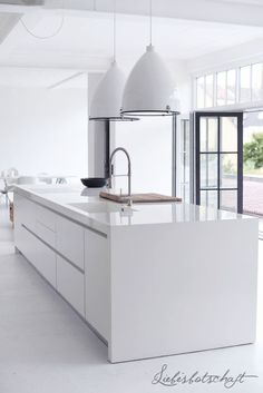 This all white kitchen is amazing.  I love the doors that lead outside.