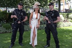 A racegoer poses for a picture next to armed police officers during day five of Royal Ascot at Ascot Racecourse in Berkshire
