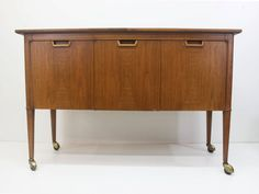 Mid Century Modern credenza/rolling bar cart made by the Mount Airy Furniture Co. Of North Carolina- Janus Collection. Walnut bar cart with contrasting Triangle walnut inlays on the doors. This Cart can be placed in the middle of a room or in a location which back is exposed, the back is finished in Walnut too! Great storage Space!  There are three drawers behind the left side door, the top drawer is felt lined. with three compartments for utensils. The right side doors open up to a large…