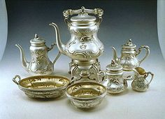 A silver tea-and-coffee service of neo-Rococo design comprising a hot water kettle, burner and stand, a coffee pot, tea pot, covered sugar bowl, creamer, waste bowl and cake dish, each chased with scrolls and rocaille and applied with a coat-of-arms - stamped with Imperial Warrant of Fabergé, assay mark of Moscow 1899-1908 , assay master Ivan Lebedkin, inventory no. 7751