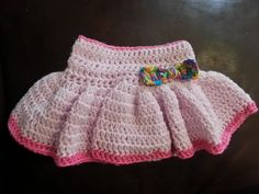 Crochet pink baby girl diaper cover with attached ruffled skirt and multi-colored bow.    Typically fits 0-3 months.      **CARE**    I recommend hand