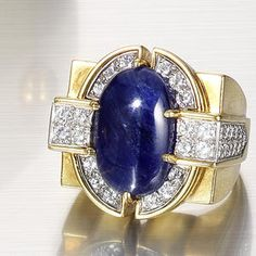 A sapphire and diamond dress ring, by Flato, circa 1940. The central oval cabochon sapphire within a brilliant-cut diamond border and shoulders, to a polished square bezel and tapering hoop, diamonds approximately 1.60 carats total, signed Flato, ring size N