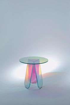 Group of low laminated and glued glass round tables, characterized by a special iridescent multicolored finish; the nuance varies according to the incidence angle of the light and to the vantage point. Objects with magical and ethereal appearance emerge.